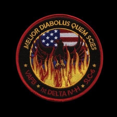 """Este parche para la misión NROL-49 representa a un ave fénix que renace de las llamas con la bandera de los Estados Unidos al fondo. Las palabras latinas """"Melior scies Quem Diabolus"""" más o menos se traducen como """"el diablo te conoce"""".Según la NASA, esta palabra se refiere al uso de un sistema antiguo después de intentar usar uno nuevo, que había resultado ser un fracaso (¿?)"""