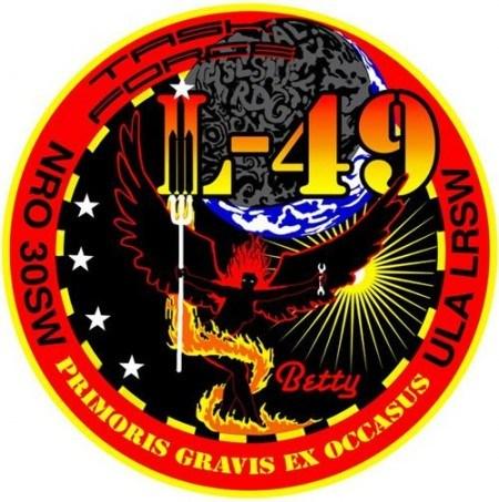 Otro parche relacionado con NRO-49 describe al satélite como un ser con alas de fuego (denominado por la NASA como un demonio llamado Betty) que está sosteniendo un tridente y una llave inglesa.