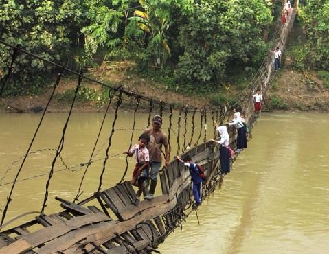 Grupo de niños y niñas cruzando sobre un puente roto a gran altura